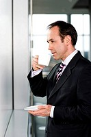 Businessman standing at office window, drinking a cup of coffee