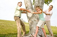 family holding hands around a tree