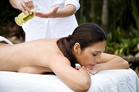 Hispanic woman receiving a massage in a tropical setting