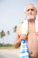 Portrait of a senior man in a swimsuit and towel at the beach