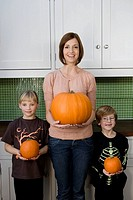 Mother and two children in the kitchen holding orange Hallowe'en pumpkins