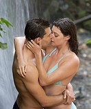 A couple kissing in a waterfall