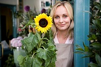 Woman florist standing at the entrance to her shop, holding a sunflower