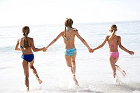 Three young girls running into the sea