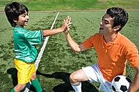 Boy and soccer coach giving high_five