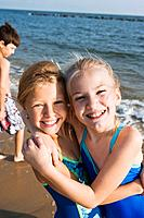 Smiling girls hugging at beach
