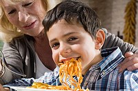 Woman and grandson eating pasta