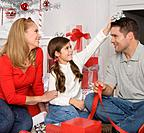 Parents and daughter wrapping Christmas gifts