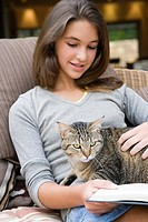 A teenage girl stroking a cat