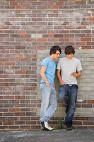 Teenage boys leaning against a wall