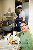 Hispanic woman eating in diner