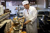 Hispanic male cook in preparing food