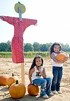 Hispanic sisters with pumpkins and scarecrow