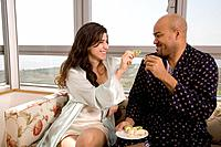 Multi_ethnic couple eating fruit