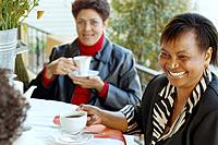 Multi_ethnic women having coffee outdoors
