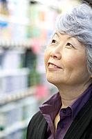 Senior Asian woman looking up