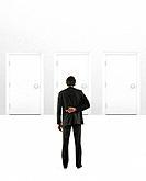 European businessman looking at doorways with fingers crossed