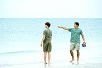 Father and teen son at the beach, man holding ball and pointing, both looking away