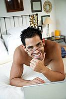 Hispanic man with laptop in bed