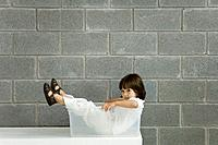 Little boy sitting inside plastic storage container, side view