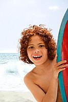 Mixed Race boy holding surfboard