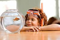 Mixed Race boy looking at fish in bowl