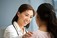 Asian doctor reassuring Hispanic female patient (thumbnail)
