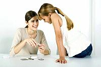 Young woman and preteen sister looking at cosmetics together, smiling