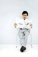 Businessman slouching in chair, reading newspaper