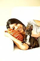 Asian woman and dog laying on sofa