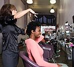 Hispanic hair stylist cutting African woman's hair