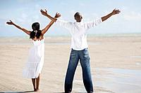 Multi_ethnic couple with arms raised at beach