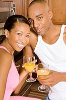 African couple holding orange juice