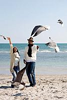 Multi_ethnic couple watching seagulls