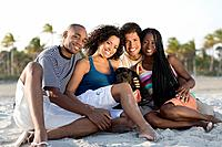 Multi_ethnic couples sitting on beach