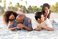 Multi_ethnic couples laying on beach