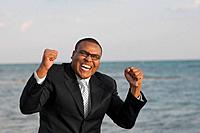 African businessman cheering in front of water