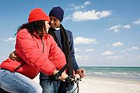 Multi_ethnic couple with bicycle at beach