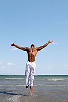 African man jumping in ocean surf