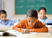 Mixed Race boy writing at school desk