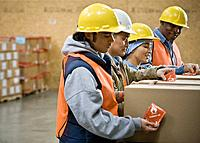 Multi_ethnic warehouse workers applying warning stickers to packages