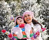 Hispanic mother and daughter in snow