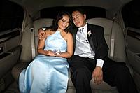 Hispanic teenaged couple hugging in limousine