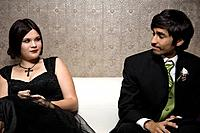 Multi_ethnic teenaged couple sitting on sofa