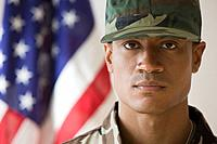 African male soldier in front of American flag