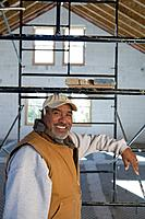 Hispanic man leaning on scaffolding
