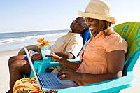 African couple relaxing on beach