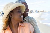 African couple hugging at beach