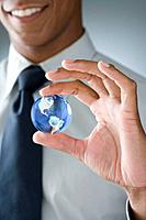 Mixed Race businessman holding glass globe