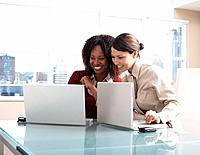 Multi_ethnic businesswomen looking at laptops
